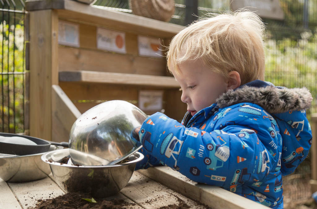 Boy playing in the mud kitchen